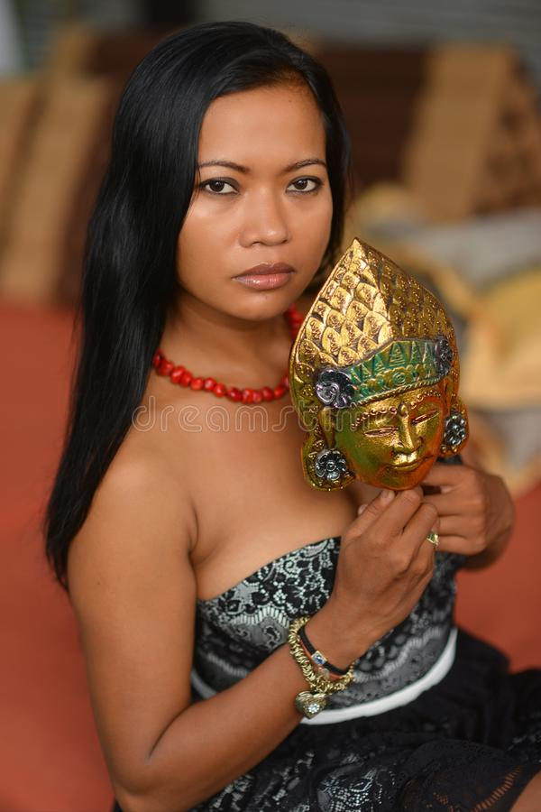 Beautiful Asian brunette model with traditional mask from Bali