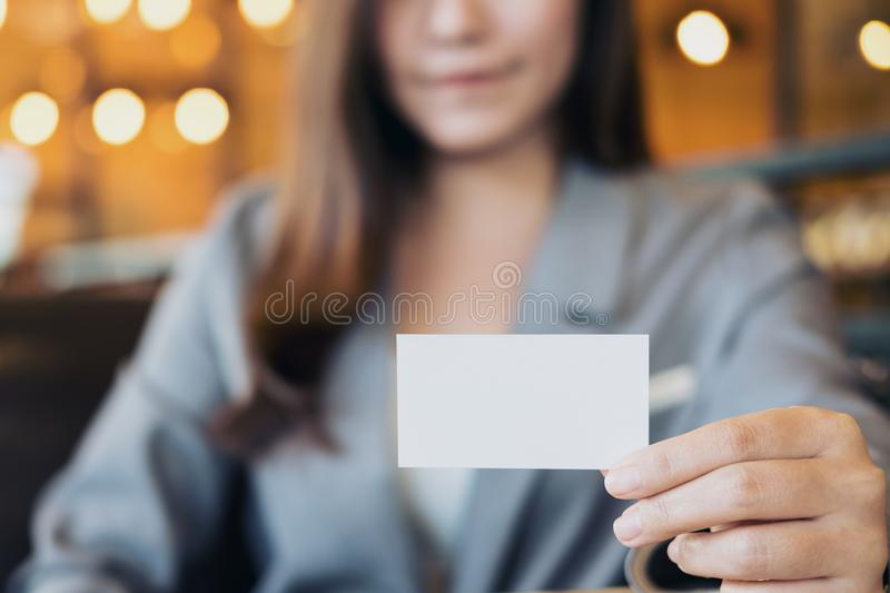 Asian business woman holding and showing empty business card in download asian business woman holding and showing empty business card in modern loft cafe stock image colourmoves