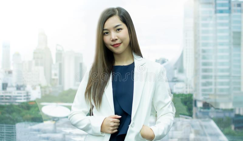 A business woman is standing beside the window in office stock photos