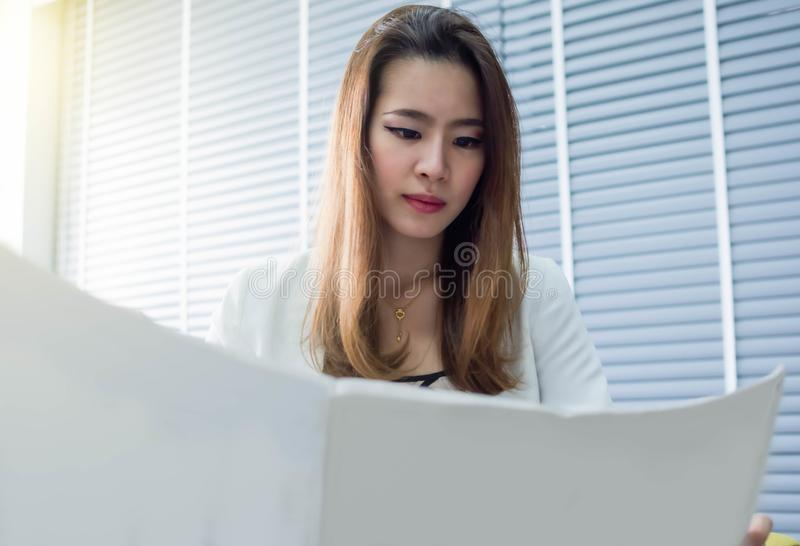 Business woman is reading newspaper in the morning royalty free stock photography