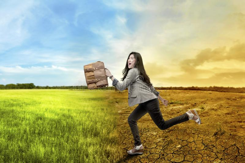 Beautiful asian business woman running with briefcase over climate change background. Global awareness concept royalty free stock image