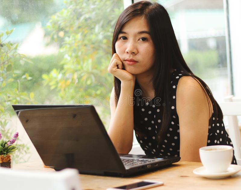 Beautiful Asian business woman sitting alone in the coffee shop with computer laptop and cup of coffee on the table hand on chin stock photos
