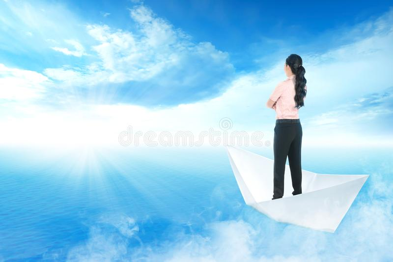 Beautiful asian business woman standing on paper boat sailing on blue ocean stock images