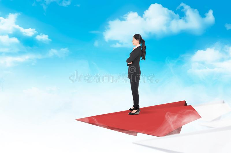 Beautiful asian business woman standing on paper plane flying royalty free stock image