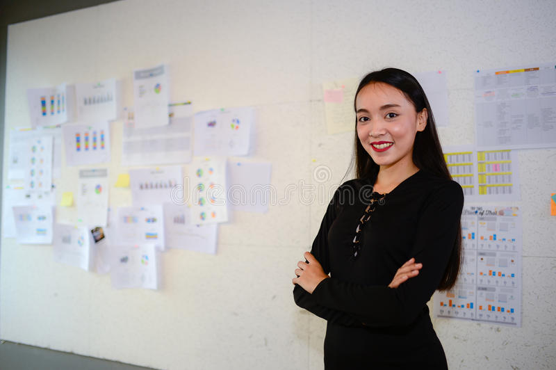 Beautiful asian business woman wear black dress, smile and stand in the office with copy space for text royalty free stock photography
