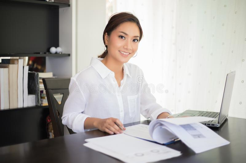 beautiful Asian business women checking document and using notebook and smiling happy for working stock images