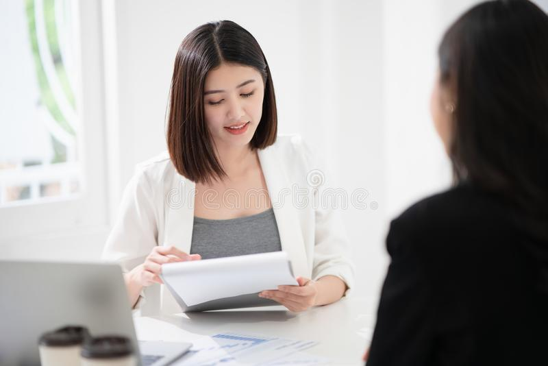 Beautiful asian business woman is reading the resume and gives the interview as a human resource for company recruitment with an royalty free stock photos