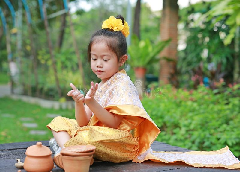 Beautiful Asian child girl in traditional thai dress play making Thai culture dessert in the public garden stock images