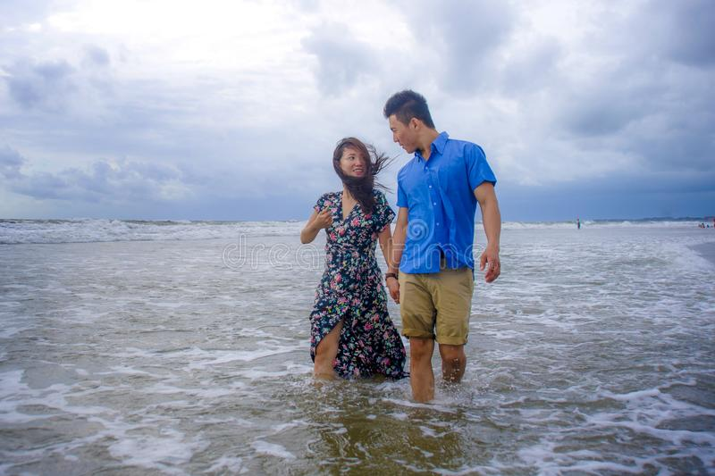Beautiful Asian Chinese couple walking together holding hands on the beach happy in love enjoying holidays royalty free stock images