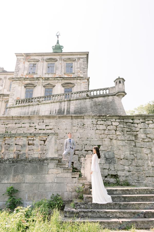 Beautiful Asian couple in luxury clothes outdoors near the castle stock photography
