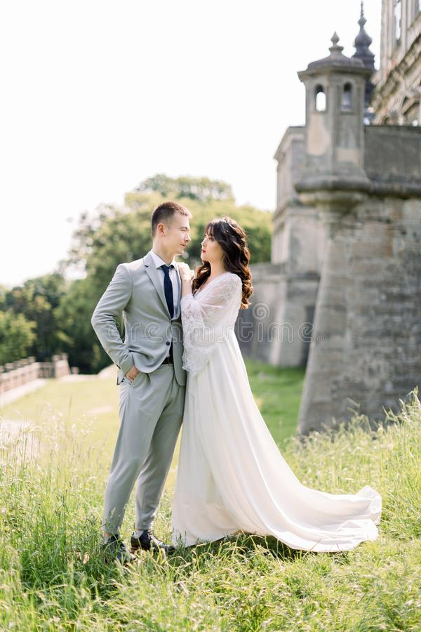 Beautiful asian couple, woman in wedding dress, man in suit, posing outdoors near the old ancient castle stock images