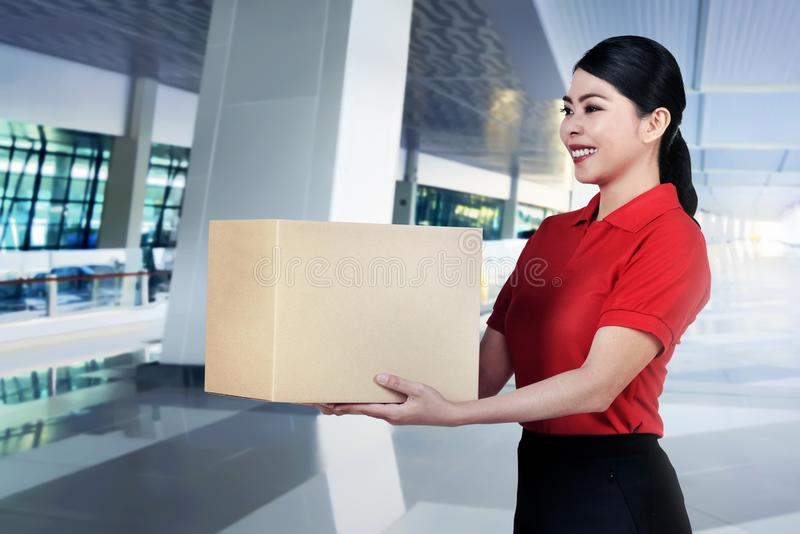 Beautiful asian courier woman bring the parcel royalty free stock photo