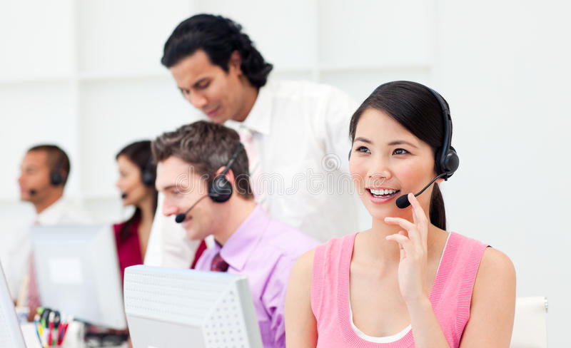 Beautiful Asian customer agent and her team stock photography