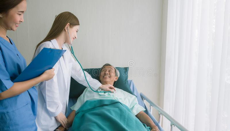 Beautiful Asian doctor listens to heart patient in hospital bed. stock photography