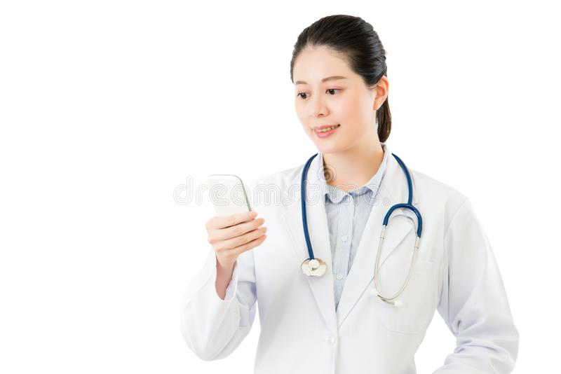 Beautiful asian doctor using smartphone isolated on white. Beautiful asian doctor using smartphone. isolated on white background. health and medical concept royalty free stock photos