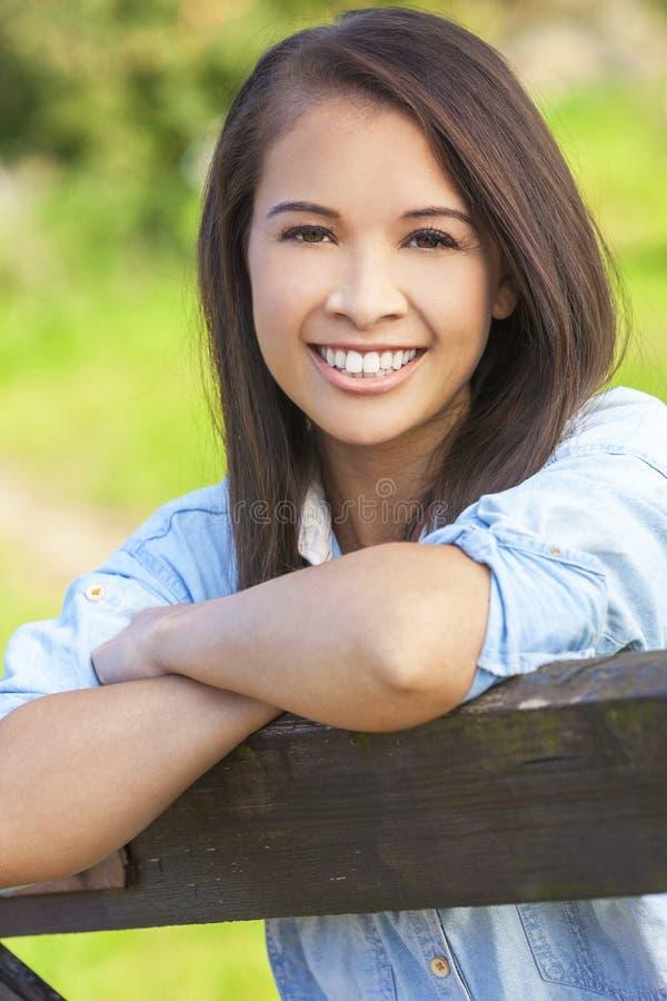 Beautiful Asian Eurasian Girl Resting on Fence stock photography