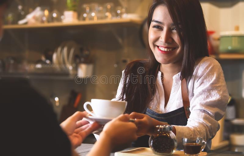 Beautiful Asian female barista serving hot coffee to customer at counter bar background. Smiling woman and occupation royalty free stock photos