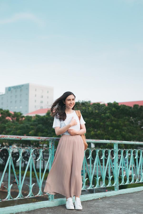 Beautiful Asian female college student holding her books standing outdoor, people education learning program college concept.  royalty free stock photos