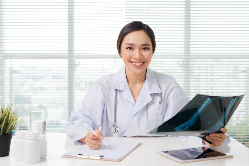 Beautiful asian female doctor examining Xray report in clinic.  stock photo