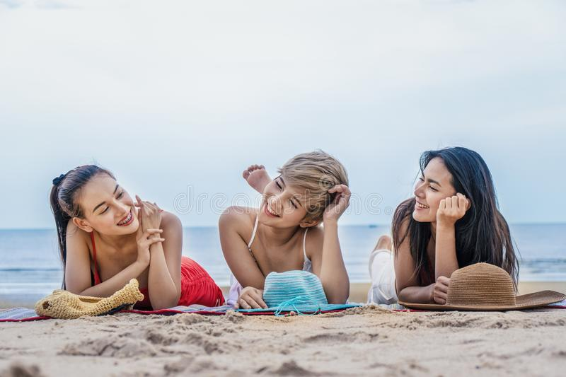 Female model friends enjoy relaxing by seaside together stock photos