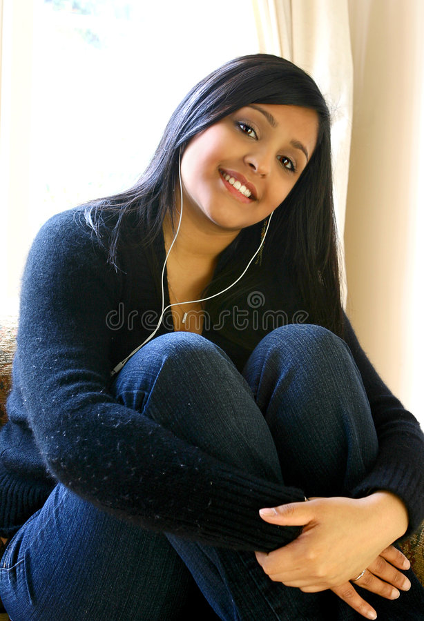 Beautiful Asian female youth listening to her favorite music in royalty free stock photo