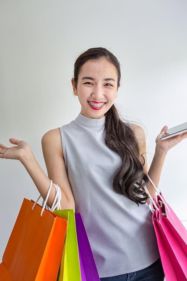 Beautiful asian girl carrying shopping bags. Shopping woman smiling. Beautiful Asian girl. young shopper stock image