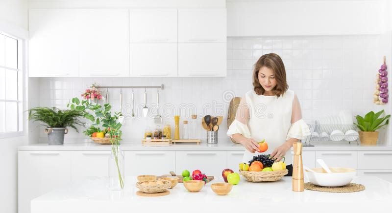 Beautiful Asian girl in casual dress is order fake fruit into wooden basket smile happily in a modern white kitchen. stock photo