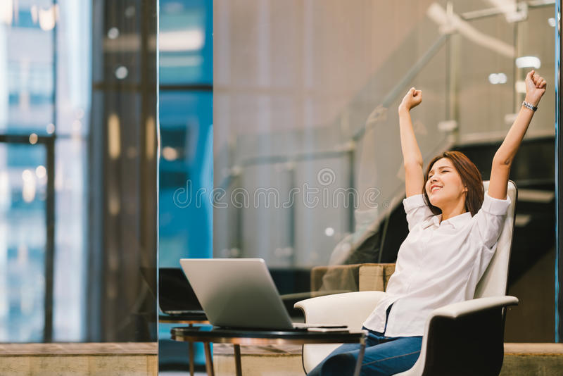 Beautiful Asian girl celebrate with laptop, hands stretch or finish work success pose. Education or technology or startup business concept, modern office or stock photos