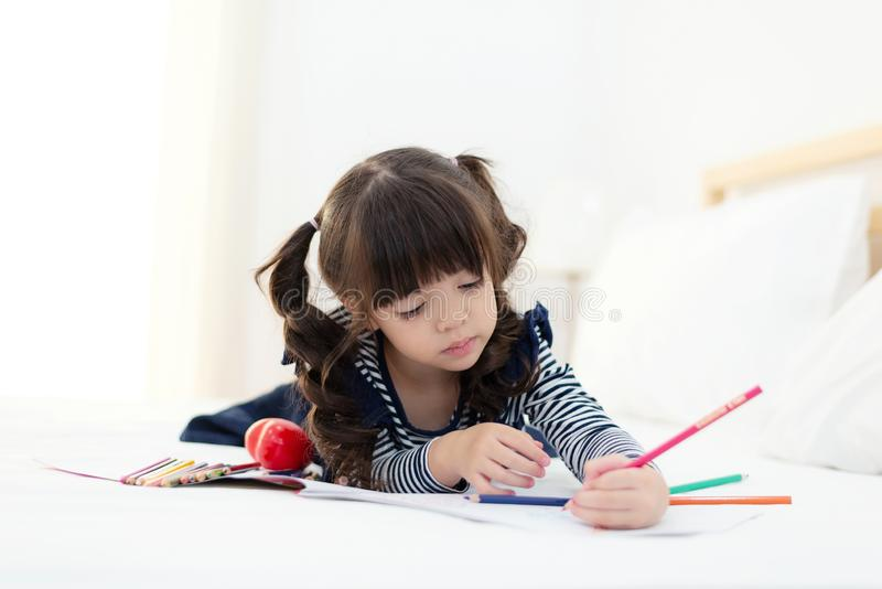 Beautiful Asian girl drawing and doing homework on the bed.  Children relax and free time for creative her play. royalty free stock image