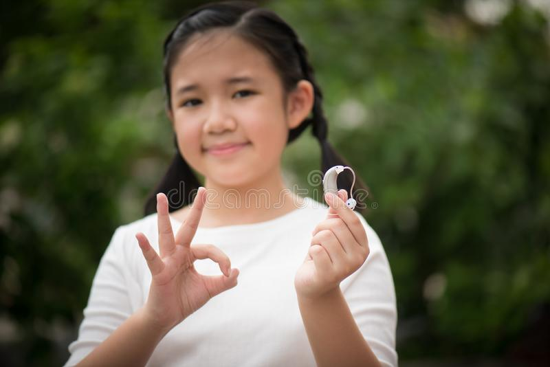 Asian girl holding hearing aid stock images