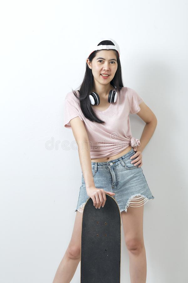 Beautiful asian girl holding skateboard stock photography