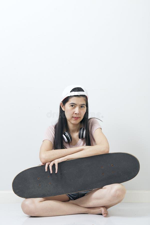 Beautiful asian girl holding skateboard stock image