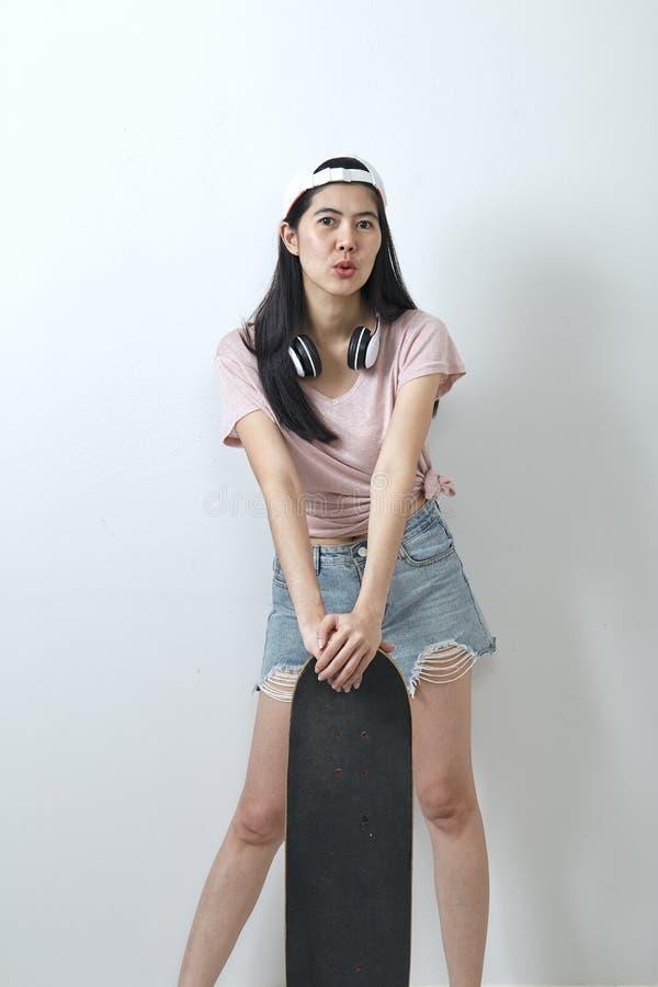 Beautiful asian girl holding skateboard royalty free stock photography