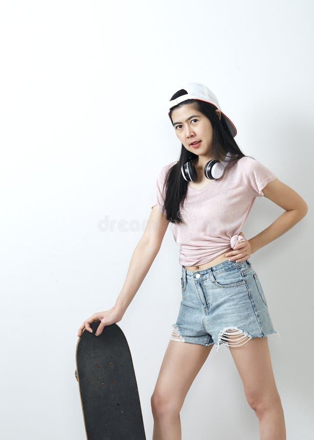 Beautiful asian girl holding skateboard stock photos