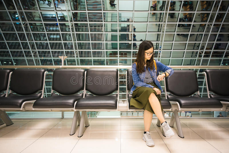 Beautiful asian girl looking at her watch, waiting to board airplane, time concept royalty free stock photography