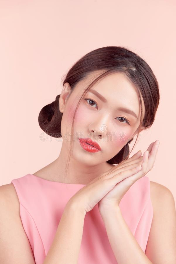 Beautiful asian girl with professional makeup and stylish hairstyle  isolated on pink. Cosmetics and make-up. Beautiful asian girl with professional makeup and royalty free stock photos