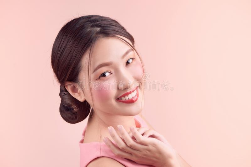 Beautiful asian girl with professional makeup and stylish hairstyle  isolated on pink. Cosmetics and make-up.  royalty free stock photo