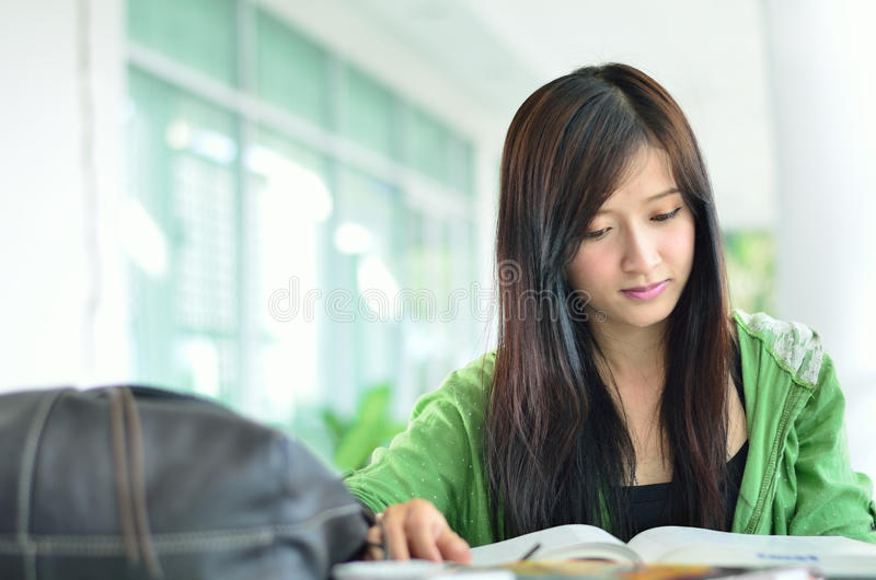Beautiful asian girl is reading. At collage view royalty free stock images