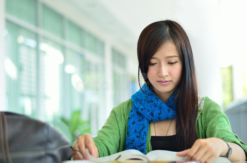 Beautiful asian girl is reading. Close up of beautiful asian girl is reading royalty free stock photo