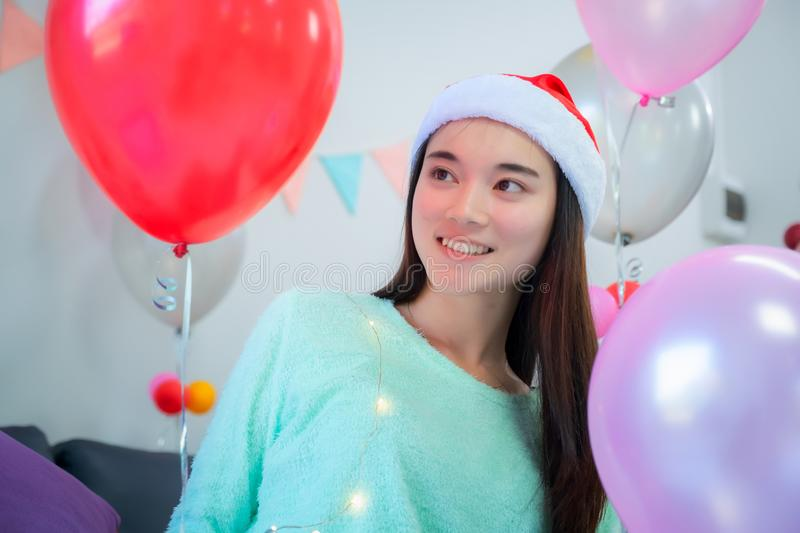 Beautiful asian girl with santa hat smiling in Christmas party with red baloon royalty free stock image