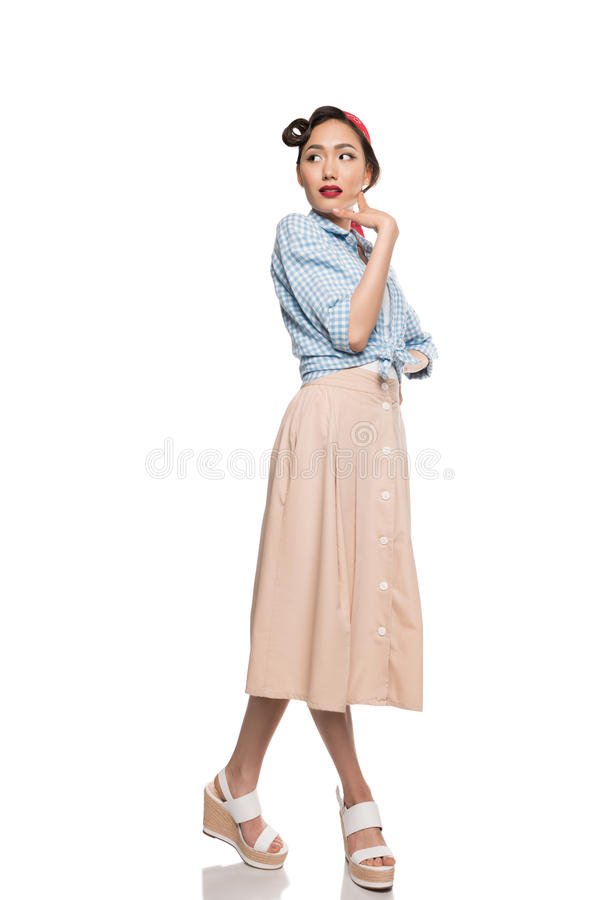Beautiful asian girl in skirt and blouse posing and looking away royalty free stock photography