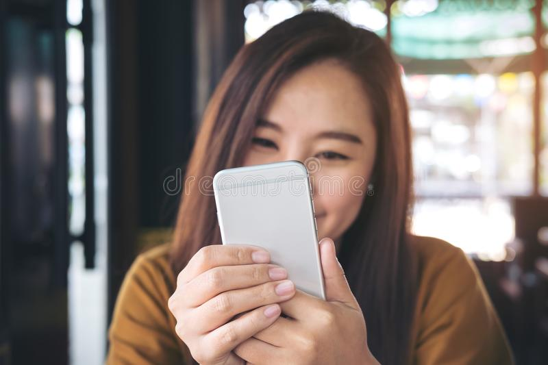 A beautiful Asian girl with smiley face holding and using smart phone royalty free stock photography