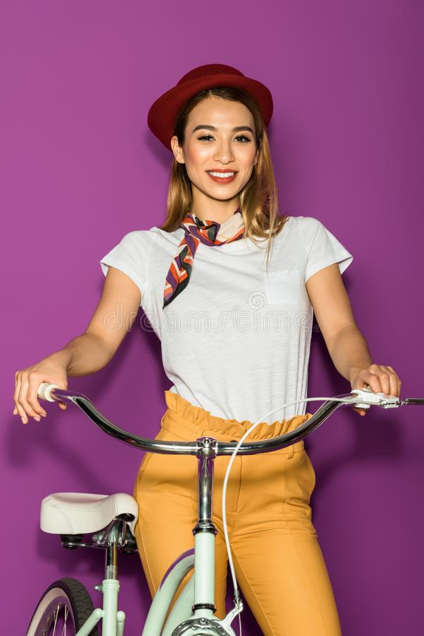 beautiful asian girl standing with bicycle and smiling at camera stock photo