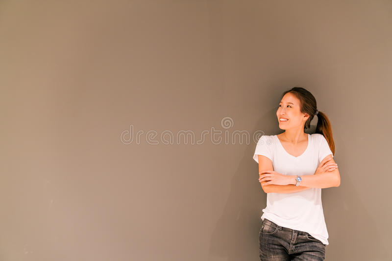 Beautiful Asian girl standing on grey wall background, looking at copy space royalty free stock photo