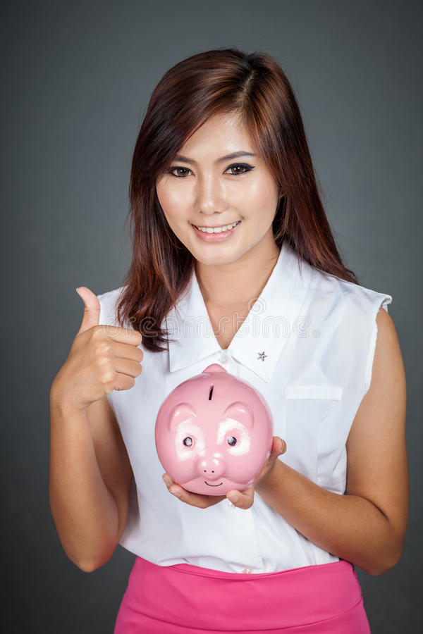 Beautiful Asian girl thumbs up with a pink pig money box. On gray background stock photos