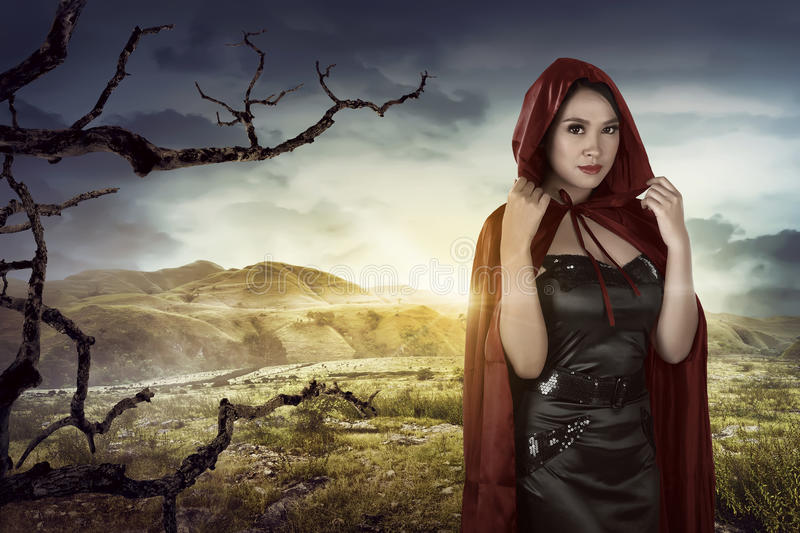 Beautiful asian girl wearing a red hooded cloak. On the dryland at sunset royalty free stock photos
