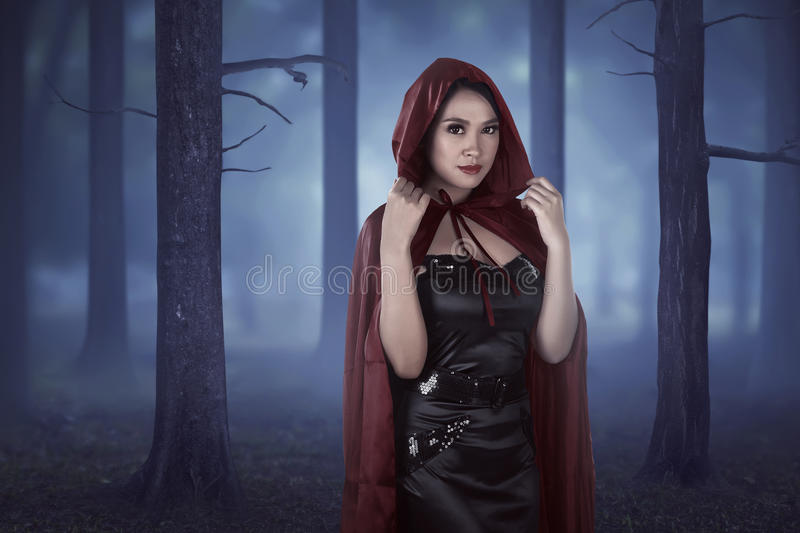 Beautiful asian girl wearing a red hooded cloak. On the forest at night stock images