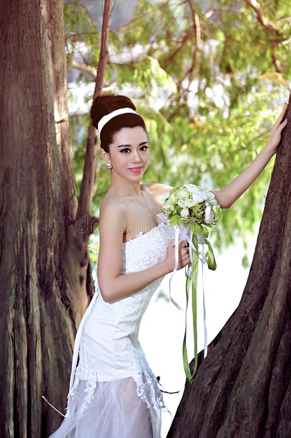Beautiful Asian girl in a wedding dress showing happy moments royalty free stock images