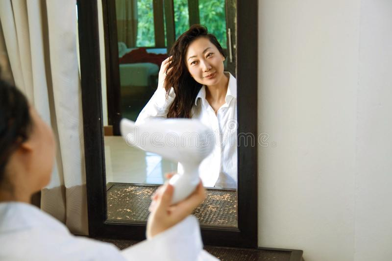 Beautiful asian girl in white drying her hair at home. Beauty, hairstyle, morning and people concept - smiling young woman with fan blow drying her hair looking royalty free stock image