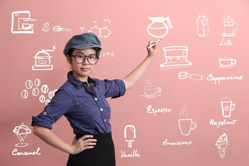 Beautiful Asian girl writing coffee menu on pink wall royalty free stock photos